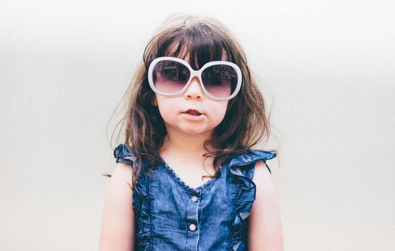Portrait Of Girl Wearing Sunglasses Against White Background