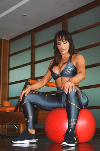 Woman sitting on fitness ball at gym