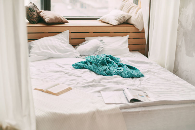On the bed in the bedroom is an open book, a blue blanket and a lot of pillows.