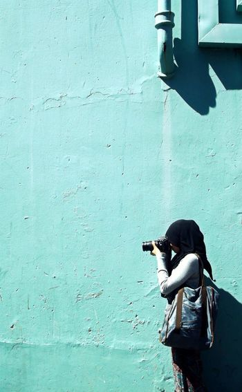 Rear view of woman photographing on mobile phone
