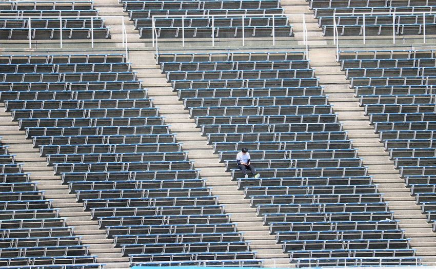 High angle view of man sitting in empty stadium