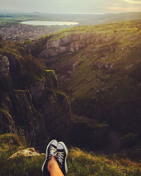 Low section of woman relaxing on cliff