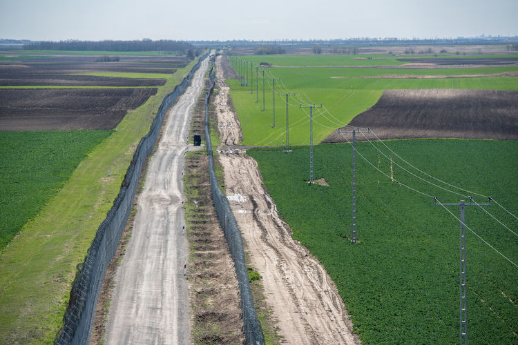 Hungarian Border Hungary Agriculture Barrier Beauty In Nature Border Border Barrier Border Fence Day Environment Farm Fence Field Grass Green Color Hungarian Border Fence Land Landscape Military Nature No People Outdoors Plant Road Rural Scene Scenics - Nature Tranquil Scene Tranquility Transportation