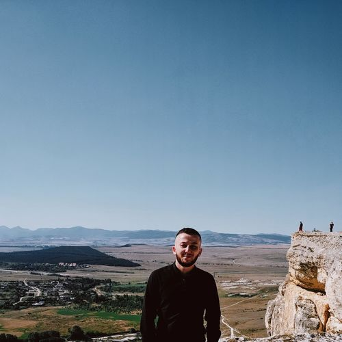 Portrait of man standing on mountain against clear sky