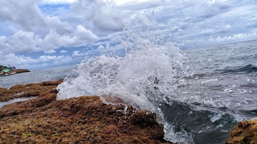 Close-up of sea wave splashing on rock against sky