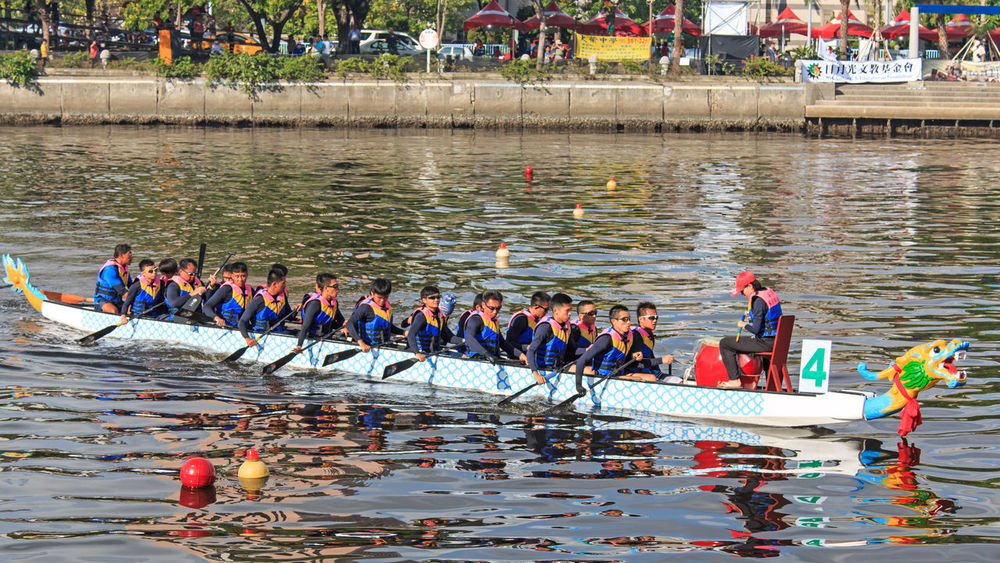 Kaohsiung, Taiwan, June 19, 2015: Boats racing in the Love River for the Dragon Boat Festival in Kaohsiung, Taiwan. The Dragon boats are the basis of the team paddling sport of dragon boat racing, a watersport which has its roots in an ancient folk ritual of contending villagers, which has been held for over 2000 years throughout southern China. For competition events, dragon boats are generally rigged with decorative Chinese dragon heads and tails. At other times (such as during training), decorative regalia is usually removed, although the drum often remains aboard for drummers to practice. Dragon boat races are traditionally held as part of the annual Duanwu Festival or Duen Ng observance in China and Taiwan. Abundance ASIA Boat Canal China Competition Day Dragon Boat Festival Hot In A Row Kaohsiung, Taiwan Large Group Of Objects Large Group Of People Leisure Activity Lifestyles Love River Mixed Age Range Mode Of Transport Multi Colored Outdoors Rippled Summer Taiwan Tropics Water