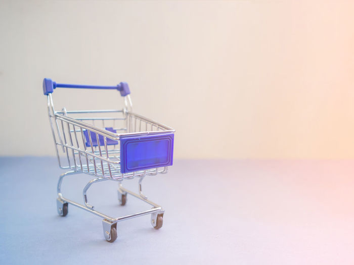 Shopping cart with sunlight effect. Absence Blue Consumerism Convenience Copy Space Empty Indoors  Metal No People Purple Retail  Shopping Shopping Cart Side View Single Object Steel Still Life Store Supermarket Trolley Wall Wall - Building Feature Wheel