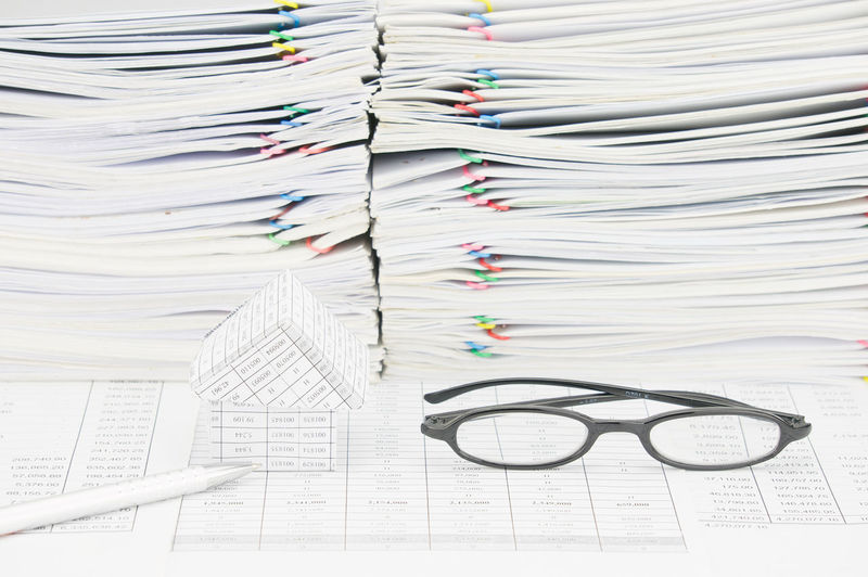 Close-up of model house with eyeglasses and pencil on financial documents