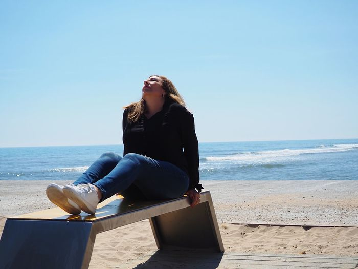 Woman sitting on seat at beach against clear blue sky