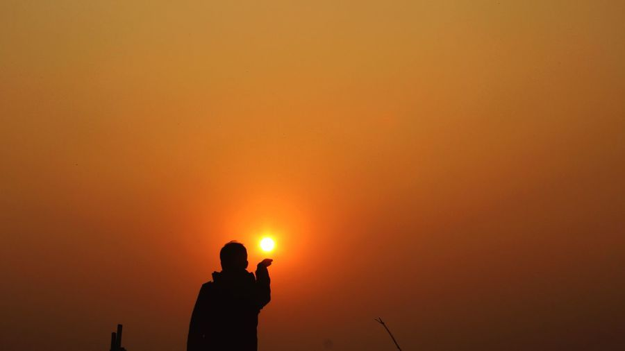 Silhouette man photographing orange sky during sunset