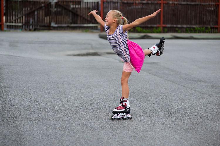 Girl Roller Skating On Road