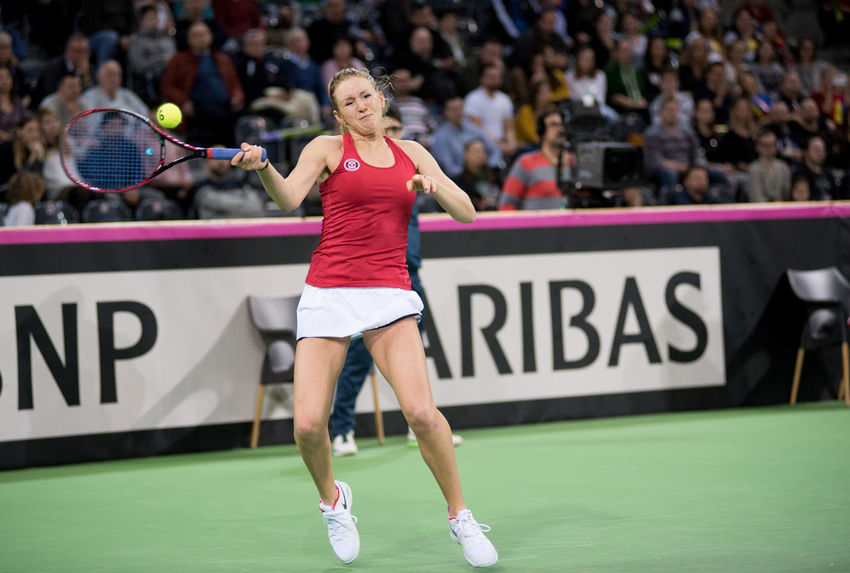CLUJ NAPOCA, ROMANIA - FEBRUARY 11, 2018: Tennis player Kathrine Sebov from Canada hitting the ball with a tennis racket during a Fed Cup match against Romania Blonde Canadian Fed Cup Romania Stadium Atmosphere Supporters Tennis Tennis Ball Tennis Player Woman Canada Concentration Crowd Fans Hitting People Playing Real People Sport Sportswear Sportswoman Tennis Racket Tennis 🎾 Tenniscourt Tribune