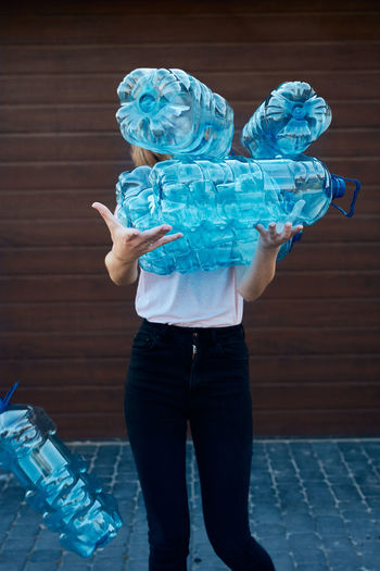 Young woman throwing out empty used plastic water bottles into trash bin. collecting plastic waste