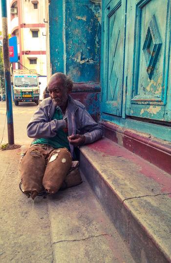 Woman sitting on door of building