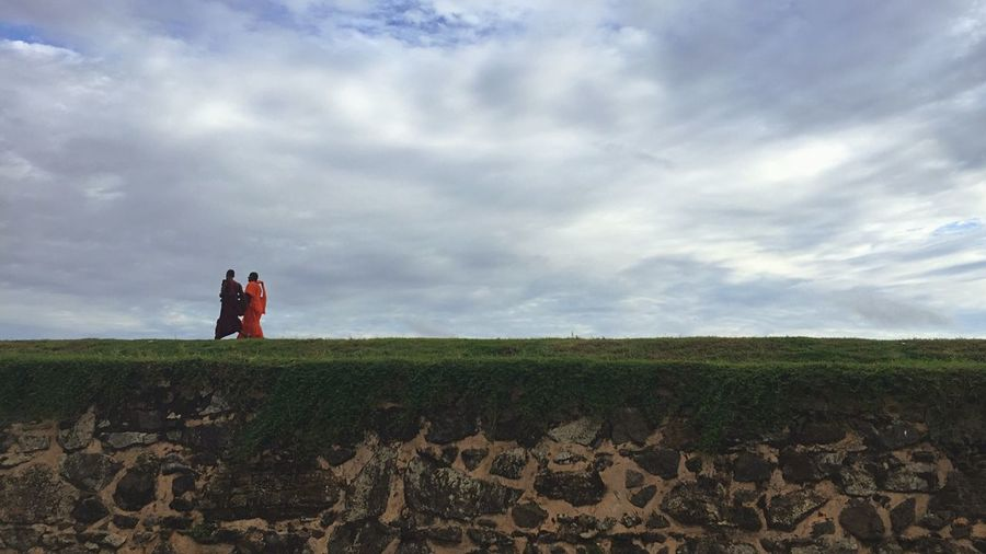Buddhist monks at galle fort against cloudy sky