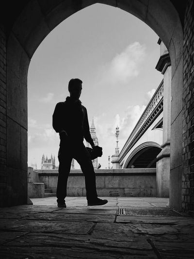 Low angle view of silhouette man walking towards archway against westminster bridge