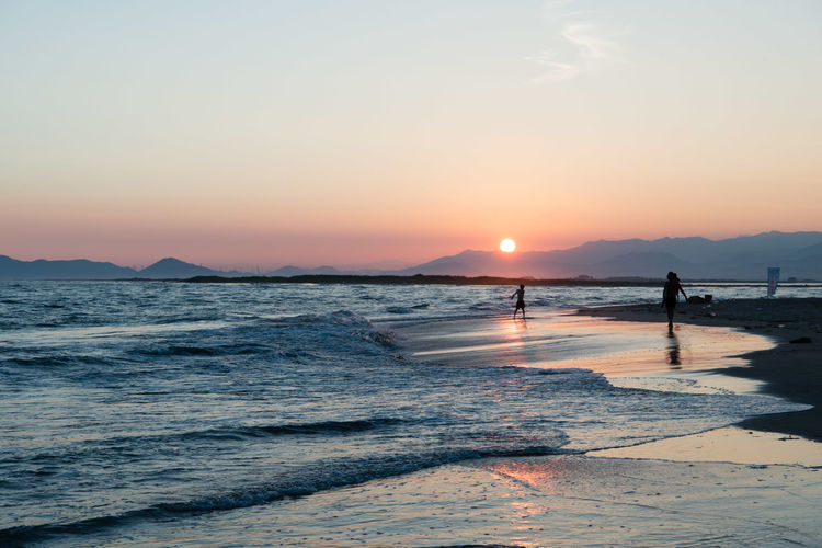 Beach Beauty In Nature Idyllic Incidental People Land Lifestyles Mountain Nature Orange Color Outdoors Real People Scenics - Nature Sea Silhouette Sky Sun Sunset Tranquil Scene Tranquility Water