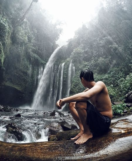 Side view of shirtless man sitting against waterfall in forest