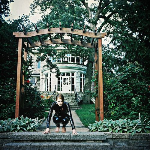 Woman Wearing Leather Suit Crouching Under Garden Pergola