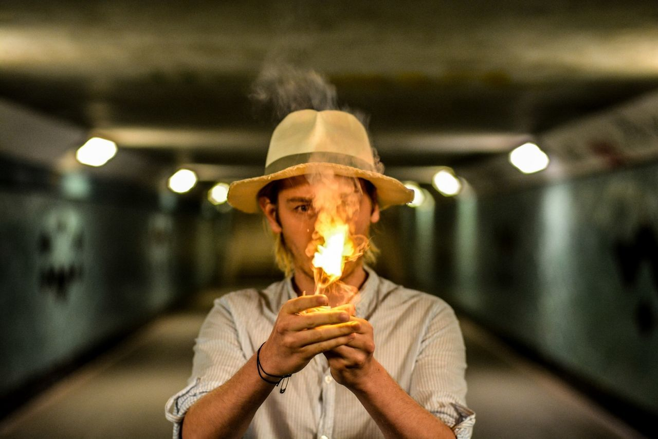 Portrait of mid adult man wearing hat holding fire while standing in tunnel