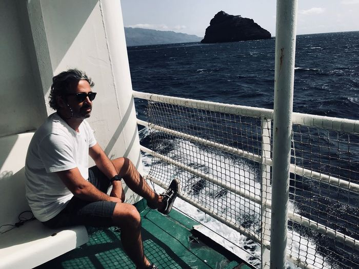 Water Sea Sitting Real People One Person Leisure Activity Glasses Sunglasses Day Lifestyles Three Quarter Length Mode Of Transportation Relaxation Casual Clothing Outdoors Men Nautical Vessel