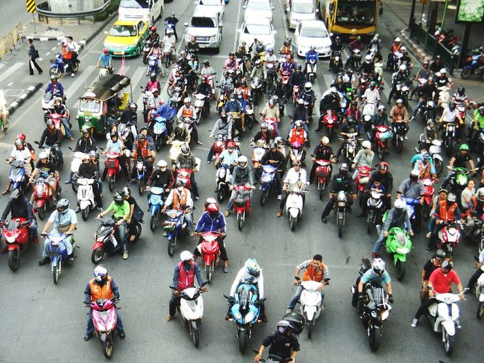 High Angle View Of People With Scooters On Road