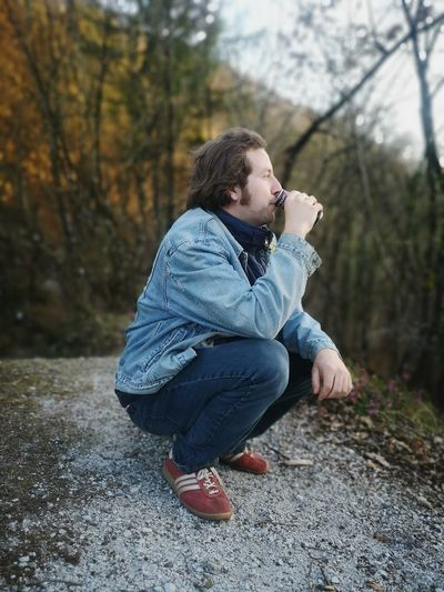 Side view of man drinking while crouching on footpath in forest