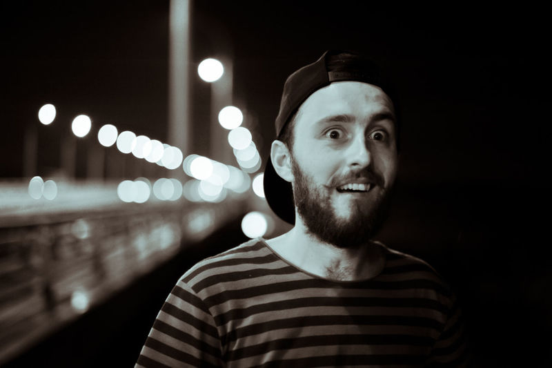 Portrait of surprised man on bridge at night