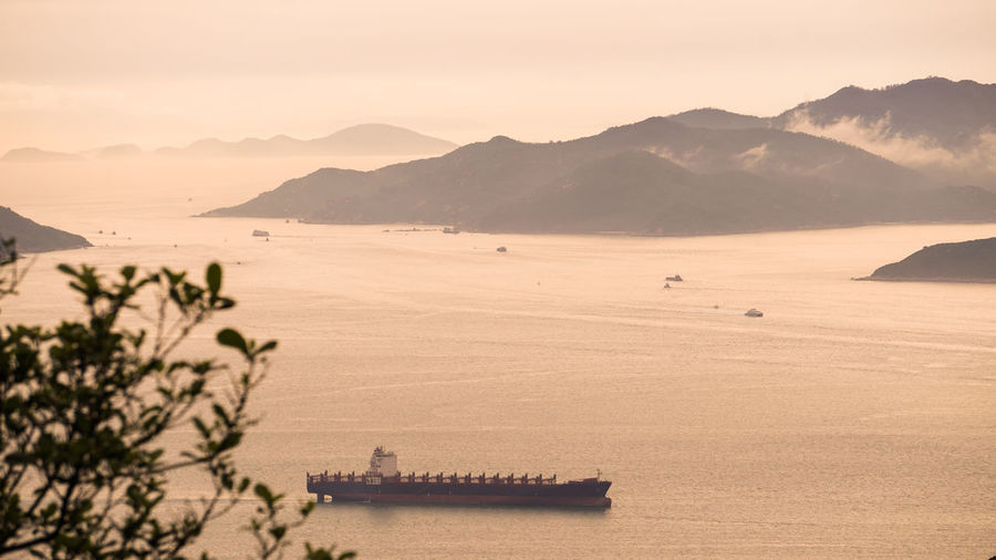 Hong kong cargo ship nuatical transportation  vessel ocean beautiful sunset mountain landscape