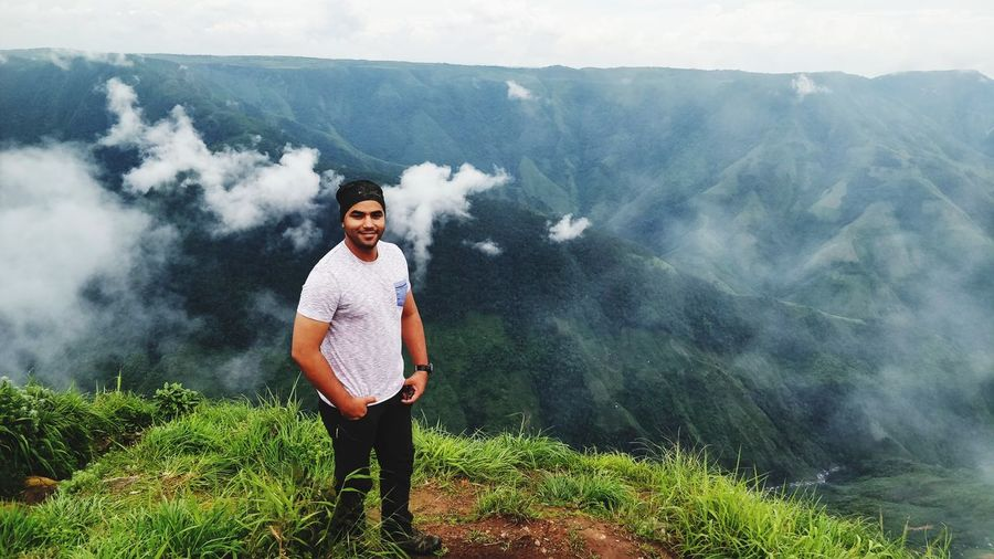 Portrait Of Smiling Young Man Standing On Mountain During Foggy Weather