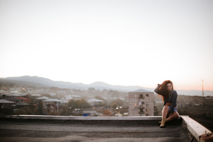 Young woman sitting outdoors during sunset