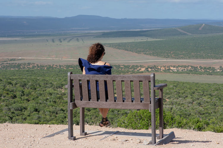 Seated One Person Leisure Activity Mountain Scenics - Nature Beauty In Nature Real People Lifestyles Non-urban Scene Environment Sitting Nature Land Landscape Tranquil Scene Rear View Casual Clothing Women Day Tranquility Plant Mountain Range Outdoors Hairstyle Looking At View