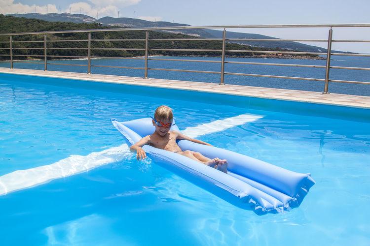 Man in swimming pool against sea