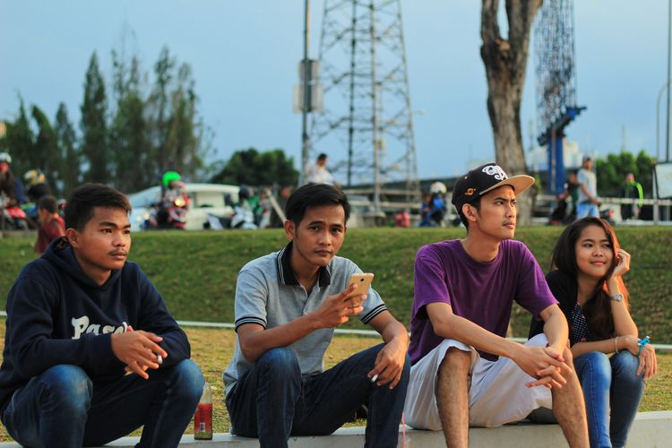 Young men sitting in park