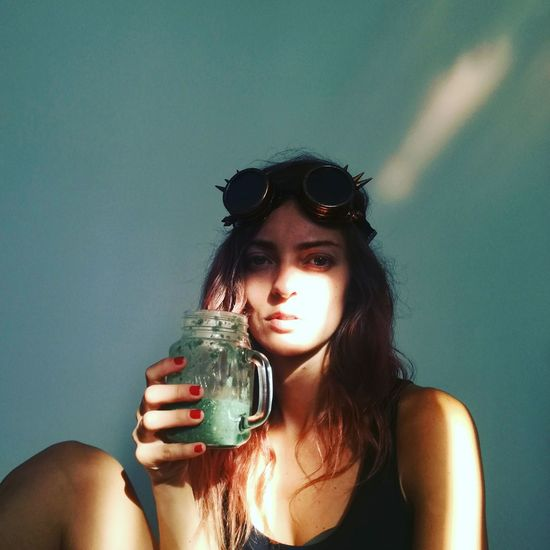 Portrait of young woman holding drink jar against wall