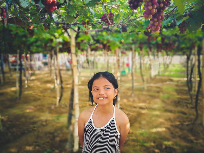 Portrait of girl standing against trees on field