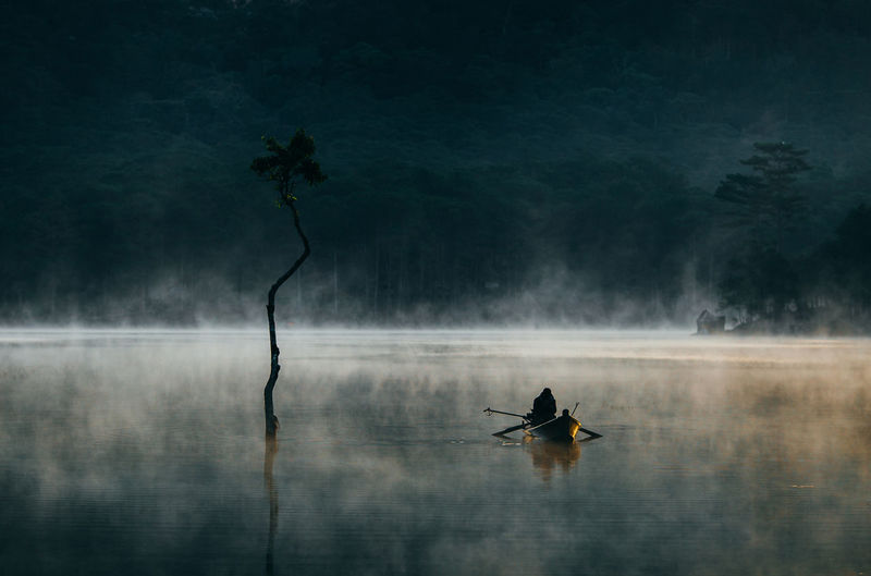 Man In Boat On Lake During Foggy Weather