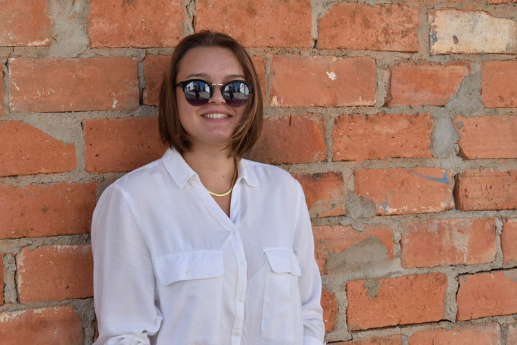 Portrait of a smiling young woman against brick wall