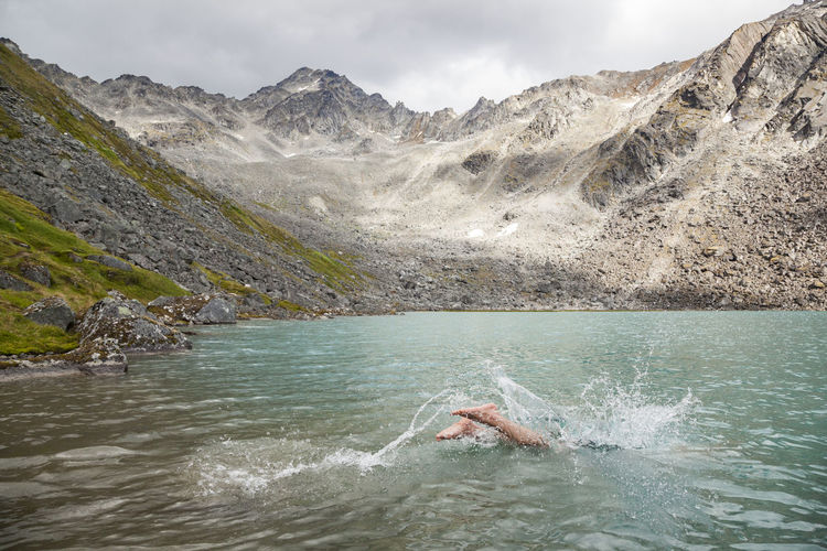 Man swimming in lake against mountains