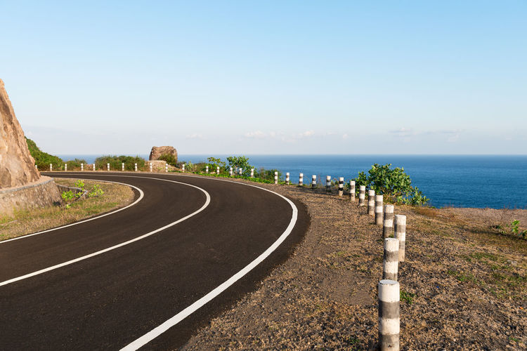 Tarmac coastal road going round cliff edge bend, with blue sea back drop. Bend Curve Road Markings White Lines Windy Road Beauty In Nature Cliff Cliff Edge Coast Road Coastal Road Day Freeway Highway Nature No People Outdoors Road Scenics Sky The Way Forward Windy