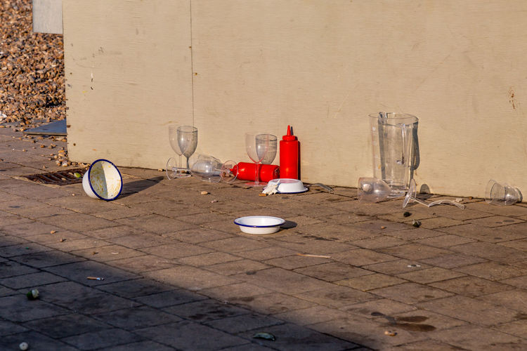 Empty food and drink packaging on the pavement after a party Absence Bottle Container Day Environment Environmental Issues Food Food And Drink Garbage Glass Glass - Material Litter No People Party Paving Stone Plastic Still Life Wall - Building Feature Waste