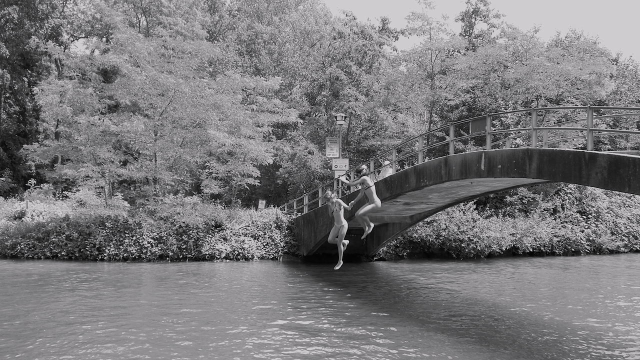 Full Length Of Women In Bikini Jumping Into River From Arch Bridge