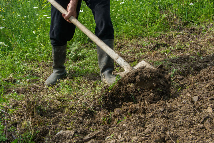 Low Section Of Man Digging Mud On Field