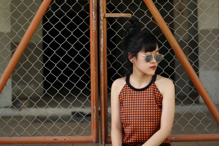 Young woman looking through chainlink fence