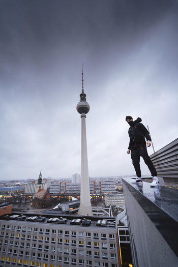 Low angle view of young man standing on building against cloudy sky