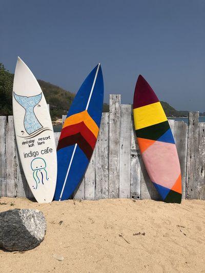 Multi colored flags on beach against clear blue sky