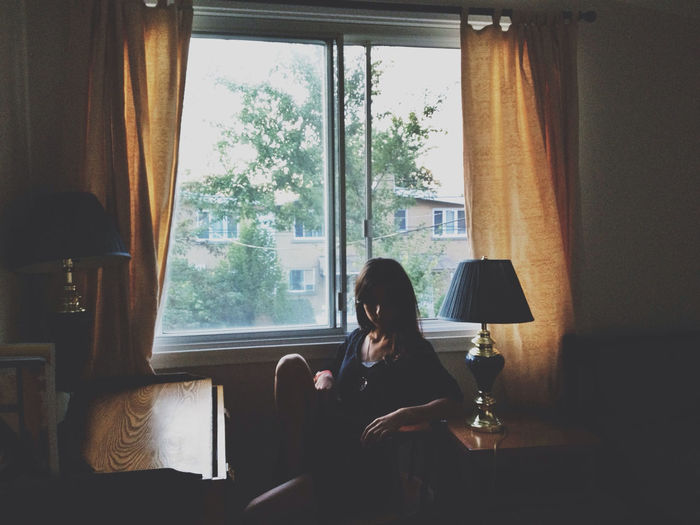 A young girl sitting alone in a dark living room