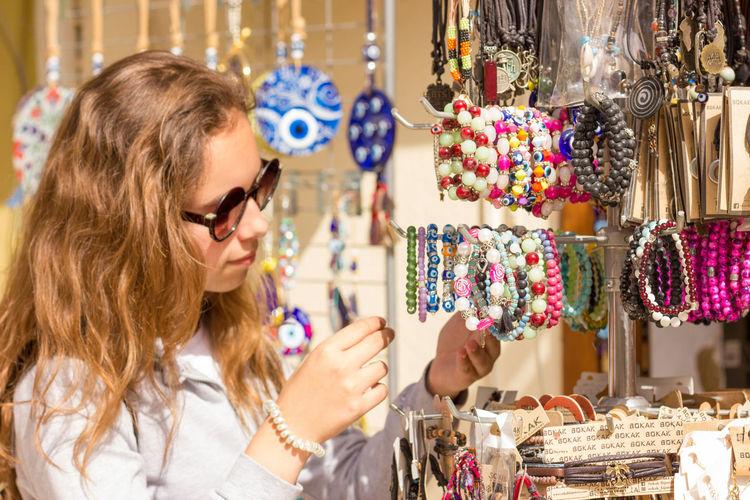 Girl wearing sunglasses buying bracelets at market stall