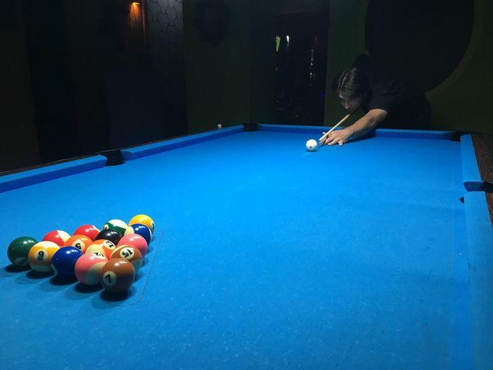 Man playing snooker in dark