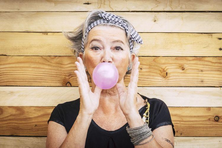 Portrait of senior woman blowing bubble gum against wooden wall